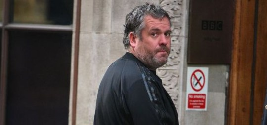 Fuming: Chris Moyles on a smoking break during his show yesterday, in which he told listeners he had slept the previous night on a friend's sofa (Picture: Rex)