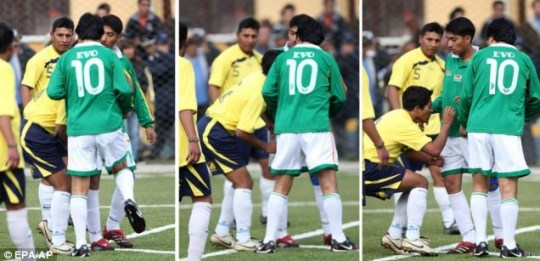 Foul play: President Evo Morales, wearing No.10, seems to knee his opponent, Daniel Cartagena, in the privates, during a football match in La Paz, Bolivia. Cartagena was sent off, naturally