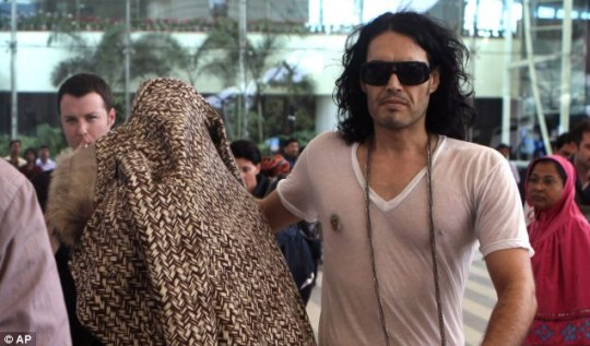 Katy Perry hides behind her coat away from cameras as she arrives with Russell Brand at the airport in Mumbai