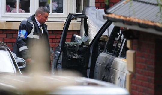 A security guard stands next to Andy Carroll's burnt out Range Rover in Ponteland (PA)