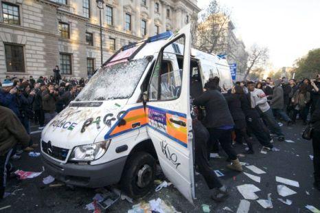 Vandalised: Rioters attack the van (Pic: London Media)