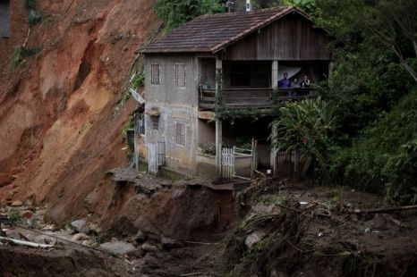 People stand on the porch of their home at the edge of landslide damage in the Caleme neighborhood in Teresopolis, Brazil
