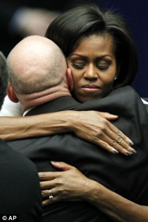 Comfort: Michelle Obama hugs Mark Kelly, husband of Mrs Giffords