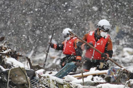Firefighters search for survivors in the snow in Minamisanriku, northern Japan