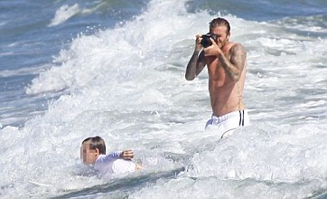 David Beckham takes to the waves as Victoria rests at home with Harper
