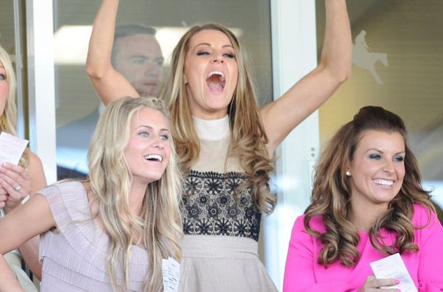 Coleen Rooney enjoys a bet in pink dress at Aintree racecourse for Liverpool Day