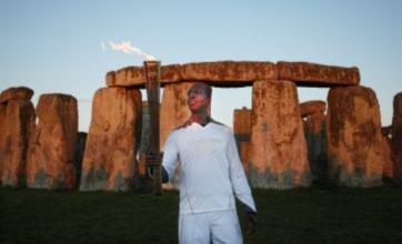 Olympic legend Michael Johnson carries torch at Stonehenge