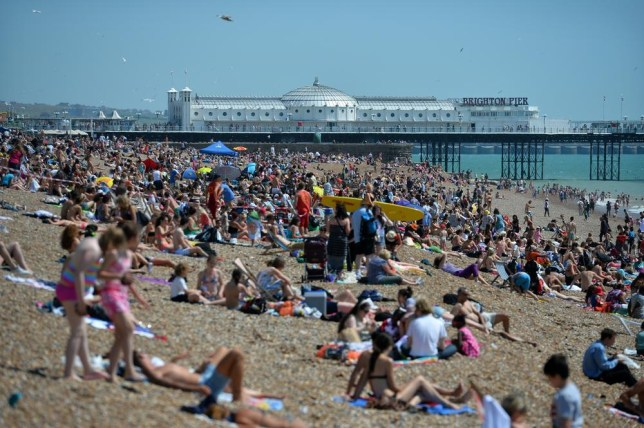 People relax in on the beach in Brighton, during hot weather on August 1, 2013