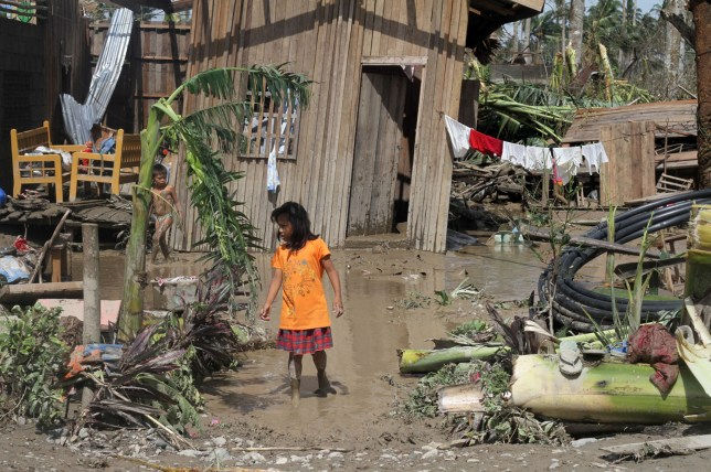 Children walk in front of their flooded home in the aftermath of Typhoon Bopha in New Bataan (Picture: AFP/Getty)