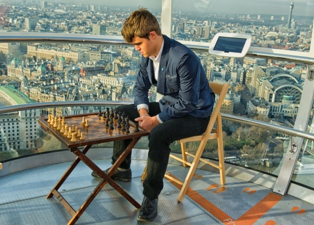 Top of the world: Magnus Carlsen studies a chess board  on the London Eye (Picture: Ray Morris-Hill)