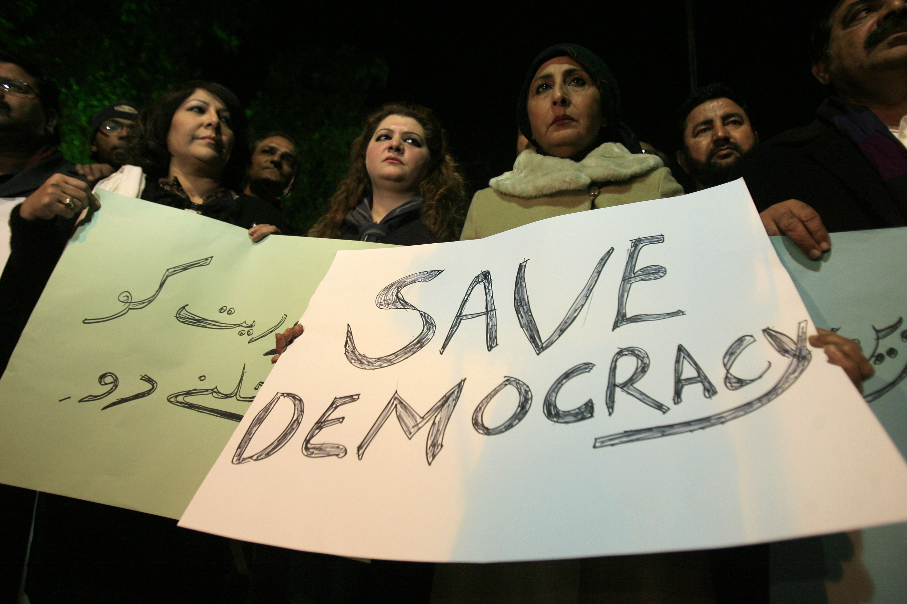 Members of the civil society hold placards during a protest against the Supreme Court decision to arrest the prime minister Raja Pervez Ashraf  in Lahore