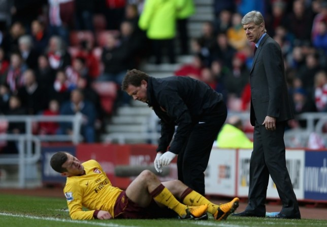 Arsenal Manager Arsene Wenger watches closley as Jack Wilshere of Arsenal is treated