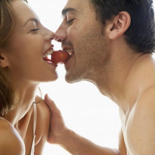 Couple eating a strawberry (source: Brooke Fasani/Corbis)