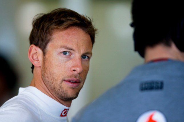 epa03627186 British Formula One driver Jenson Button of McLaren Mercedes talks to a team member before the third practice session at the Albert Park circuit in Melbourne, Australia, 16 March 2013. The 2013 Formula One Grand Prix of Australia will take place on 17 March 2013.  EPA/DIEGO AZUBEL