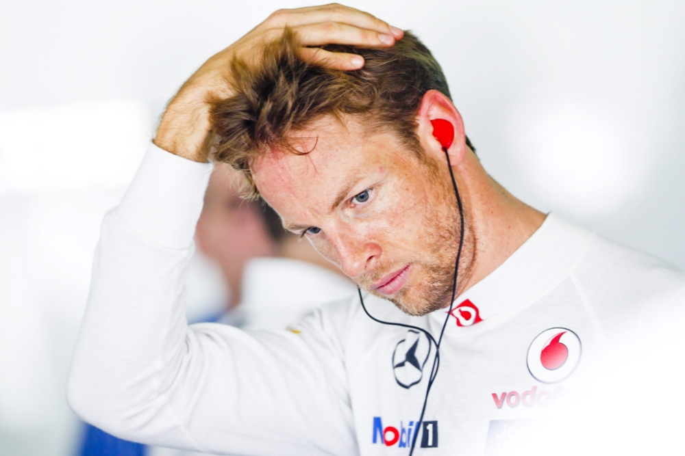 epa03637292 British Formula One driver Jenson Button of McLaren Mercedes is seen inside the team garage, during the 3rd practice session for Malaysia Formula one Grand Prix at Sepang International Circuit, near Kuala Lumpur, 23 March 2013. The Malaysian Grand Prix will be held on 24 March.  EPA/DIEGO AZUBEL