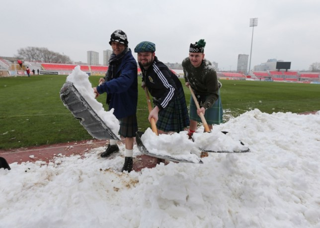 Scotland fan Dougie McKinlay (centre) with his friends help clear snow from the pitch in the stadium before the FIFA World Cup Qualifying, Group A match at Karaorde Stadium, Novi Sad, Serbia. PRESS ASSOCIATION Photo. Picture date: Tuesday March 26, 2013. See PA story SOCCER Scotland. Photo credit should read: Andrew Milligan/PA Wire. RESTRICTIONS: Use subject to restrictions. Editorial use only. Commercial use only with prior written consent of the Scottish FA. Call +44 (0)1158 447447 for further information.