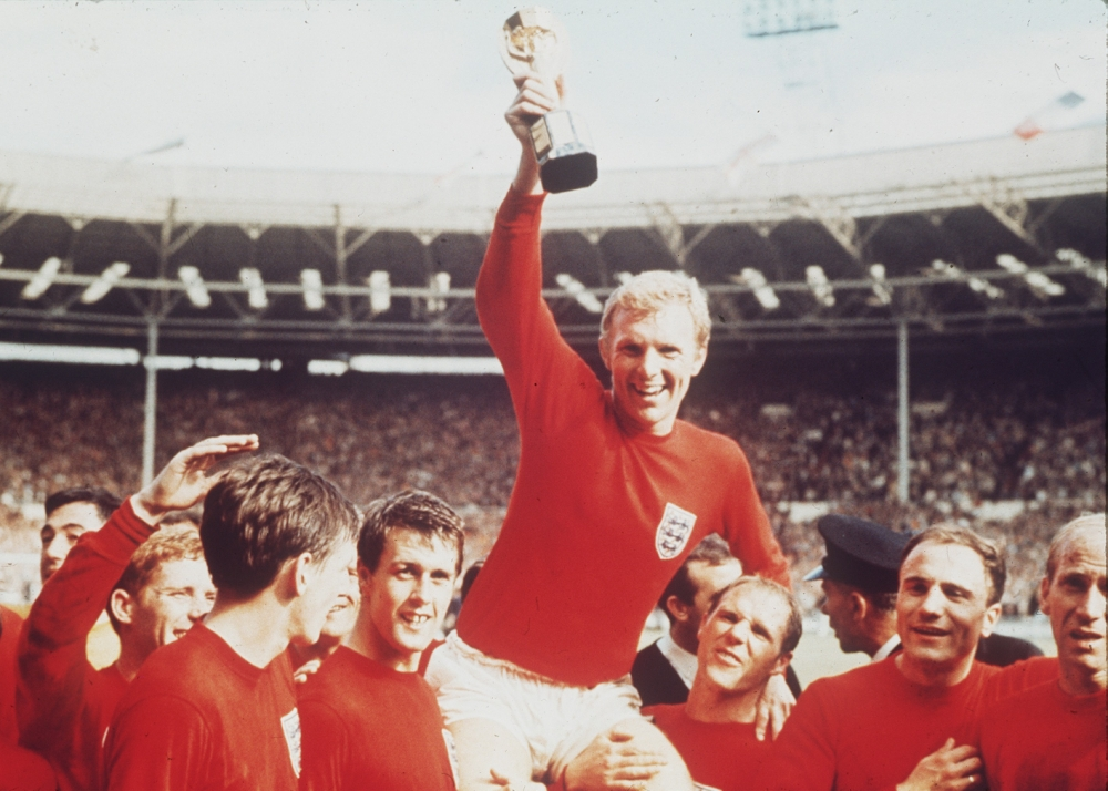 FILE - The July 30, 1966 file photo shows England's soccer captain Bobby Moore, carried shoulder high by his team mates, holding aloft the World Cup trophy. England defeated Germany 4-2 in the final, played at London's Wembley Stadium. From left to right, goalkeeper Gordon Banks (partially obscured), Alan Ball, Martin Peters, Geoff Hurst, Moore, Ray Wilson, George Cohen and Bobby Charlton. Another Germany vs. England match at the World Cup brings back memories of classic moments that include a disputed goal in the final, the English losing a 2-0 lead, and a dramatic shootout win for the Germanys. The two teams meet in the last 16 on Sunday and could well write another chapter in one of soccer's most famous rivalries. (AP Photo)