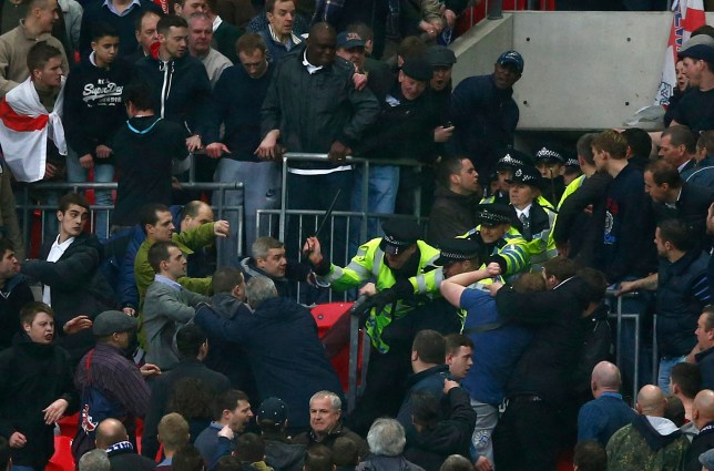 Millwall fans fight with police officers during their FA Cup semi-final soccer match against Wigan Athletic at Wembley Stadium in London