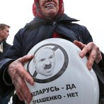 """A Belarusian opposition protester holds a  balloon with the image of Belarusian President Alexander Lukashenko during a rally in Minsk, Belarus, Sunday, March 24, 2013, on the eve of what they call Freedom Day. March 25 has long been a traditional day of demonstration for the opposition, marking the anniversary of the 1918 declaration of the first, short-lived independent Belarusian state. The sign reading """"Belarus - yes, Lukashenko - no"""". (AP Photo/Sergei Grits)"""