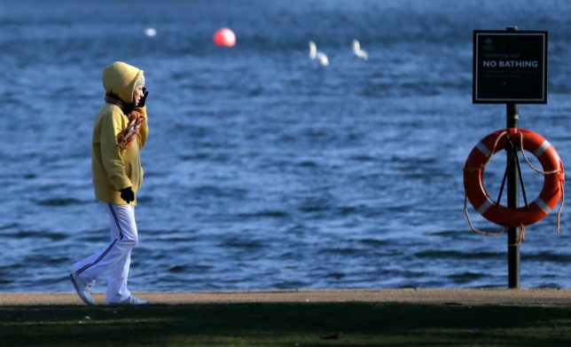 A women wrapped up against the cold walks along the Serpentine lake in Hyde Park,