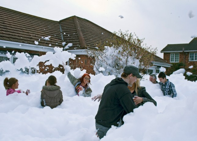 A friendly feud involving two neighbours saw Barry Brennand return from holiday to find his garden transformed into a zoo. Barry got his own back on Maggie Mcelroy after hiring a foam gun and pouring 6 feet of snow into her garden, in Rhyl, North Wales. Pictured, friends and neighbours have fun in the foam. © WALES NEWS SERVICE