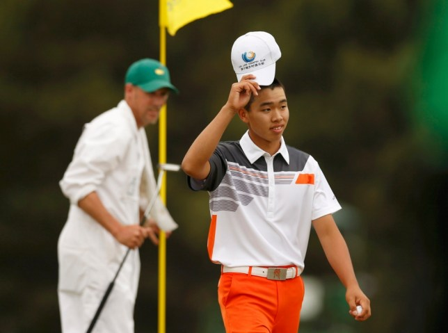 Amateur Guan Tianlang of China tips his hat after sinking a par putt on the 18th green during final round play in the 2013 Masters golf tournament at the Augusta National Golf Club in Augusta, Georgia, April 14, 2013.   REUTERS/Mark Blinch (UNITED STATES  - Tags: SPORT GOLF)