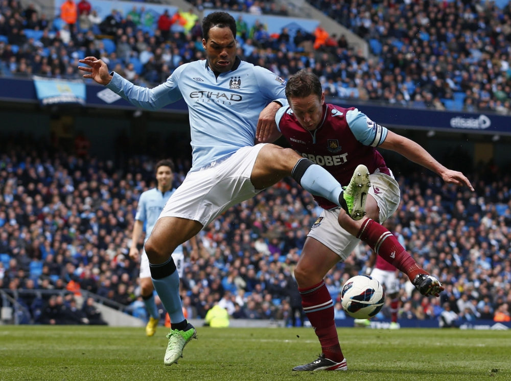"Manchester City's Joleon Lescott (L) challenges West Ham United's Kevin Nolan for the ball during their English Premier League soccer match at The Etihad Stadium in Manchester, northern England, April 27, 2013. REUTERS/Darren Staples (BRITAIN - Tags: SPORT SOCCER) FOR EDITORIAL USE ONLY. NOT FOR SALE FOR MARKETING OR ADVERTISING CAMPAIGNS. NO USE WITH UNAUTHORIZED AUDIO, VIDEO, DATA, FIXTURE LISTS, CLUB/LEAGUE LOGOS OR ""LIVE"" SERVICES. ONLINE IN-MATCH USE LIMITED TO 45 IMAGES, NO VIDEO EMULATION. NO USE IN BETTING, GAMES OR SINGLE CLUB/LEAGUE/PLAYER PUBLICATIONS"