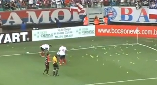 Another fine mess: Players of both teams begin clearing the trumpets off the pitch (Picture: YouTube)