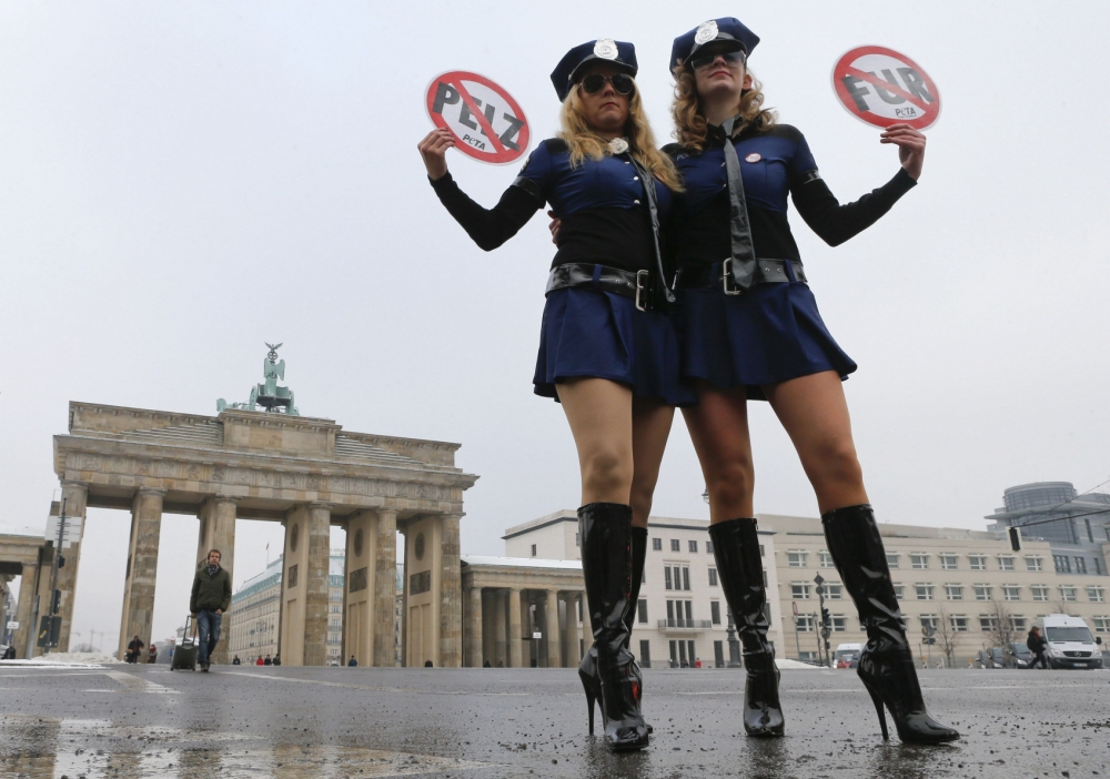 PETA animal rights group activists protest against the use of fur in front of the Brandenburg Gate outside the venue of the Berlin Fashion Week Autumn/Winter 2013 in Berlin January 15, 2013.  REUTERS/Fabrizio Bensch (GERMANY - Tags: FASHION CIVIL UNREST)