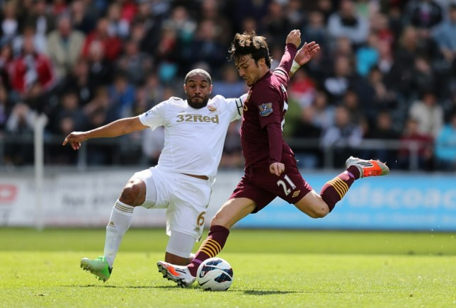 Swansea City's Ashley Williams attempts to block the shot from Manchester City's David Silva during the Barclays Premier League match at the Liberty Stadium, Swansea. PRESS ASSOCIATION Photo. Picture date: Saturday May 4, 2013. See PA story SOCCER Swansea. Photo credit should read: David Davies/PA Wire. RESTRICTIONS: Editorial use only. Maximum 45 images during a match. No video emulation or promotion as 'live'. No use in games, competitions, merchandise, betting or single club/player services. No use with unofficial audio, video, data, fixtures or club/league logos.
