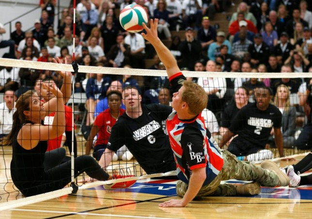 epa03696931 Britain's Prince Harry hits the ball to former U.S. Olympic beach volleyball great Misty May-Treanor (L) as they play sitting volleyball with the U.S. forces and UK forces team at a visit to the Warrior Games at the US Olympic Training Center in Colorado Springs, Colorado, USA, 11 May 2013.  EPA/RICK WILKING / POOL