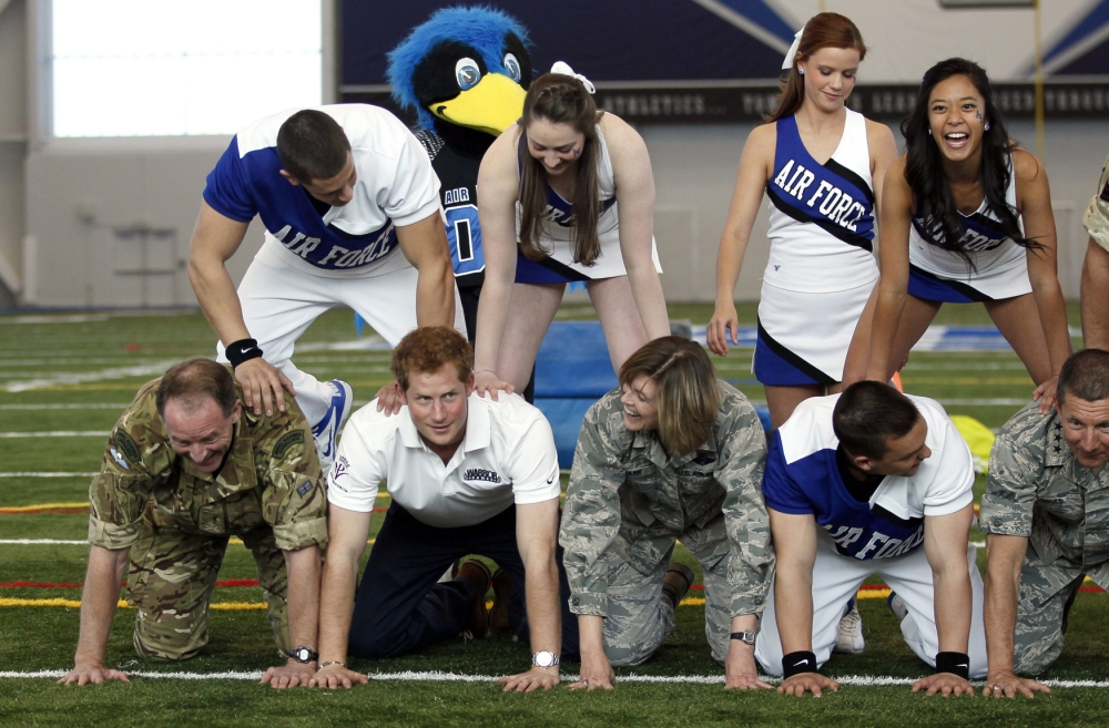Prince Harry impresses as a quarterback and props up human pyramid during US visit