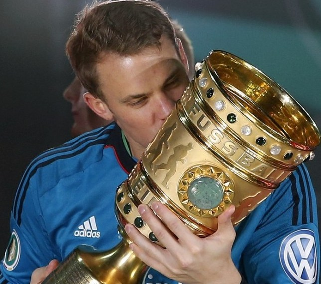 You beauty: Neuer kisses the German Cup after Bayern's victory over Stuttgart last week (Picture: AP)