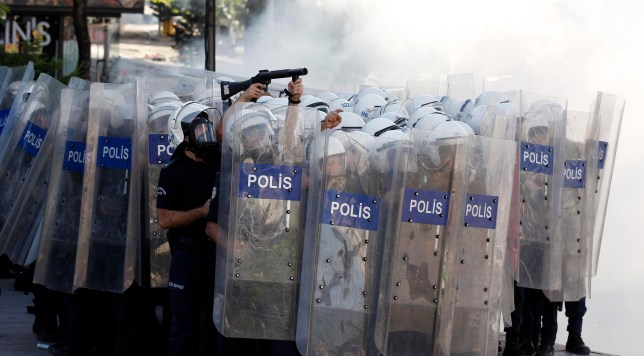 Riot police behind shields fire tear gas during clashes with demonstrators protesting against Turkey's Prime Minister Tayyip Erdogan (Picture: Reuters)