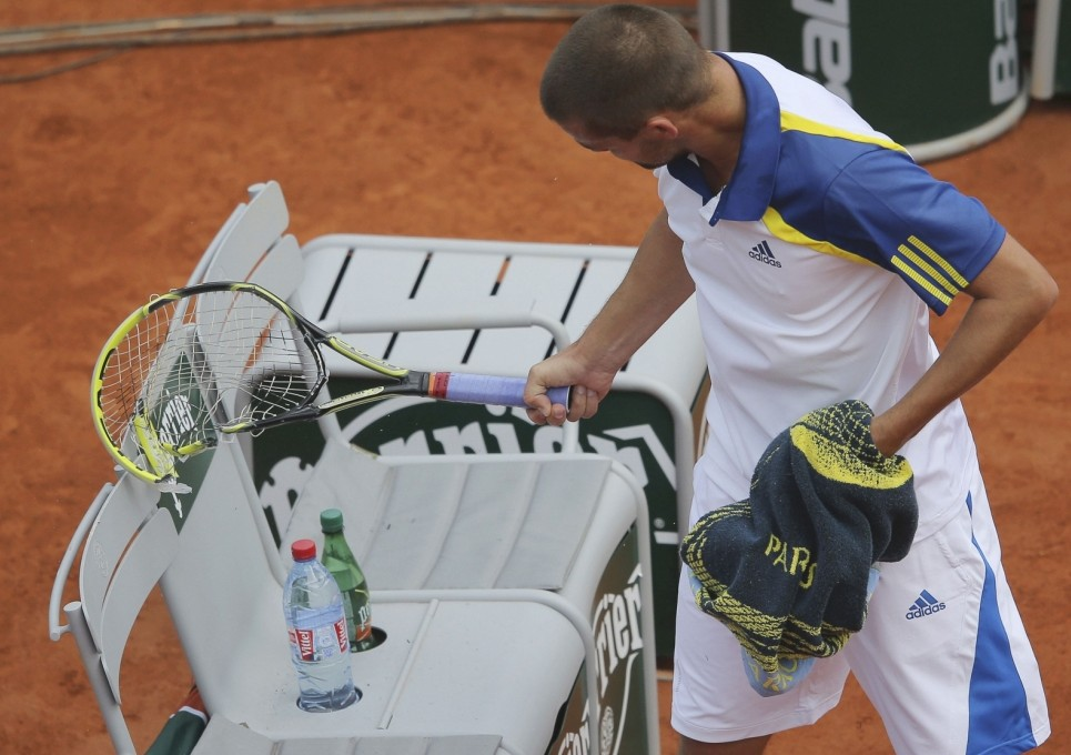 Mikhail Youzhny of Russia looks at his broken racket after mangling it following a lost point during his men's singles match against Tommy Haas of Germany at the French Open tennis tournament at the Roland Garros stadium in Paris June 3, 2013. REUTERS/Stephane Mahe (FRANCE  - Tags: SPORT TENNIS)