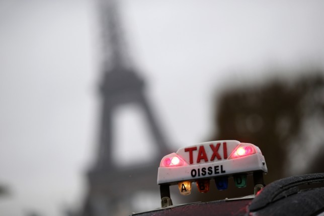 A photo taken on January 10, 2013 shows a taxi light with the Eiffel tower in the background during a nationwide demonstration in Paris to protest against legislative changes concerning the transport of sick and incapacitated passengers.  AFP PHOTO / KENZO TRIBOUILLARD        (Photo credit should read KENZO TRIBOUILLARD/AFP/Getty Images)