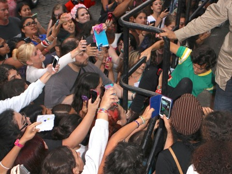 Harry Styles takes evasive action to crawl under railing as he's mobbed by frenzied fans