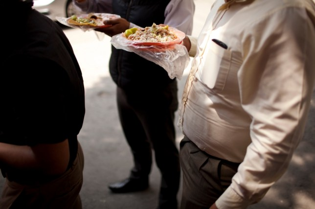 Office workers eats tacos at an outdoor food stand during lunch time in Mexico City, Wednesday, July 10, 2013. Mexico has surpassed the United States in levels of adult obesity. Almost one-third of adult Mexicans, 32.8 percent, are obese compared to 31.8 percent of Americans, according to the U.N. Food and Agriculture Organization, or FAO. (AP Photo/Ivan Pierre Aguirre)