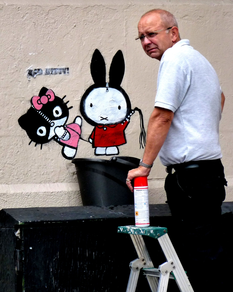 PIC FROM CATERS NEWS - (PICTURED: The Kitty piece by DS) - This is the moment a clever graffiti artist decided to immortalise a man sent to remove his artwork - by turning him into the ART. Stencil artist - who is known only as DS - created his first piece Bad Kitty on a wall in London as an amusing comment on the squeaky clean image of the Hello Kitty character. DS, who is 28, and from London, created his artwork in May but eight hours later he was surprised to see someone already in the process of removing it. Deciding to document the act of erasing his work, DS took photos of the moment and then used one to show the man that removed it. SEE CATERS COPY.