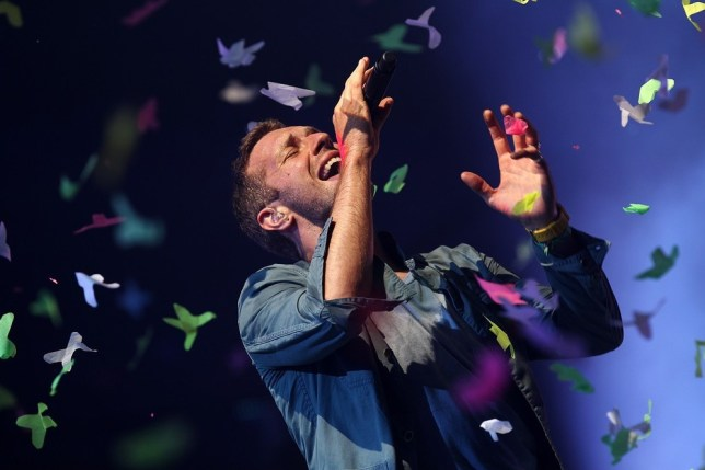 Chris Martin wore a mask to get the party started at Arcade Fire gig (Picture: AFP/Getty)