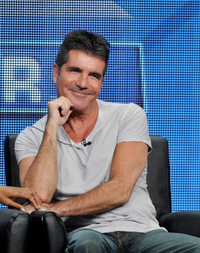 "Simon Cowell, a judge on the FOX series ""The X Factor,"" smiles from the stage during a panel discussion on the show at the FOX 2013 Summer TCA press tour at the Beverly Hilton Hotel on Thursday, Aug. 1, 2013, in Beverly Hills, Calif. (Photo by Chris Pizzello/Invision/AP)"