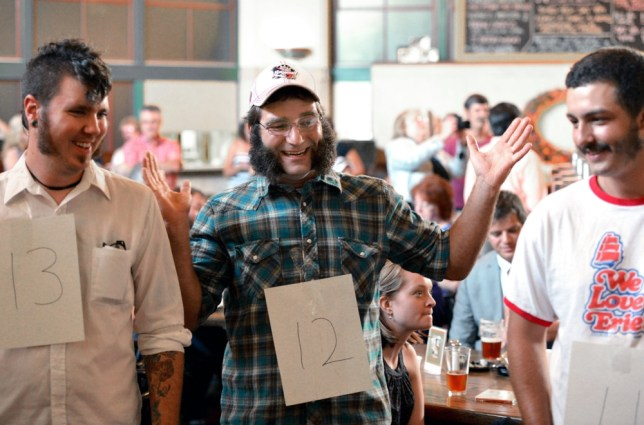 Roman Glass, left, 30, of Erie, Pa,, Jeremy Krol, center, 33, of Waterford, Pa., and Nick Bird 19, of Erie, Pa, participate in a sideburns contest that honors a U.S. Navy commodore known for his impressive facial hair, Wednesday, Aug. 7, 2013 at the Brewerie at Union Station in Erie, Pa. (AP Photo/Erie Times-News, Jarid A. Barringer)  TV OUT; MAGS OUT; COMMERCIAL INTERNET OUT