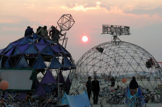 Participants watch the sunrise from the top of a dome at the 2013 Burning Man arts and music festival, in the Black Rock Desert of Nevada, August 29, 2013. The federal government issued a permit for 68,000 people from all over the world to gather at the sold out festival, which is celebrating its 27th year, to spend a week in the remote desert cut off from much of the outside world to experience art, music and the unique community that develops. REUTERS/Jim Bourg (UNITED STATES - Tags: SOCIETY) FOR USE WITH BURNING MAN RELATED REPORTING ONLY. FOR EDITORIAL USE ONLY. NOT FOR SALE FOR MARKETING OR ADVERTISING CAMPAIGNS. NO THIRD PARTY SALES. NOT FOR USE BY REUTERS THIRD PARTY DISTRIBUTORS