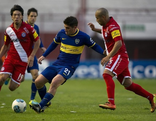 Toothless: Iniguez, right, fights fot the ball with Boca Junior' Cristian Erbes (Picture: AFP/Getty Images)