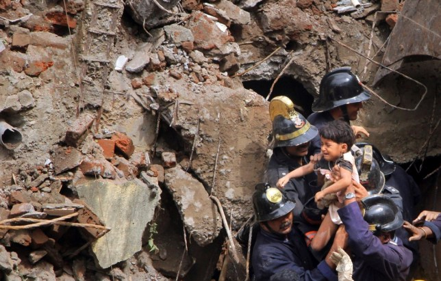 Indian Fire officials rescue a girl from debris of a collapsed building in Mumbai, India, Friday, Sept. 27, 2013. The multi-story residential building collapsed in India's financial capital of Mumbai early Friday, killing at least three people and sending rescuers racing to reach dozens of people feared trapped in the rubble. (AP Photo)