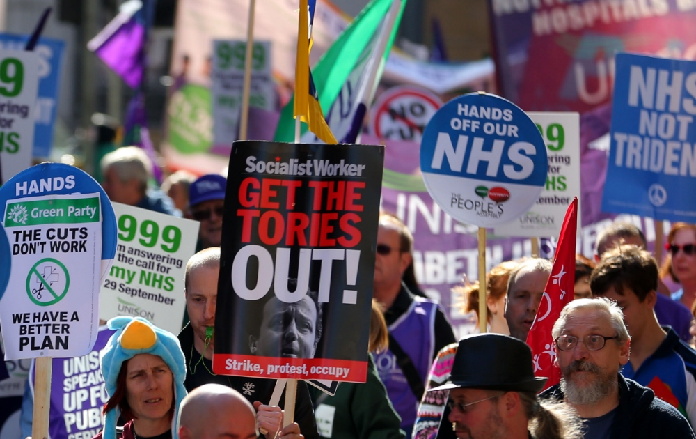 Protesters march through Manchester on a union protest against austerity cuts on the opening day of the Conservative Party conference