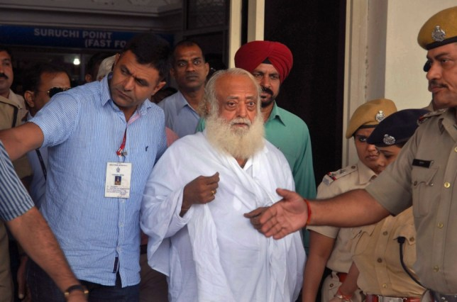 Controversial spiritual guru Asaram Bapu, center, is brought for interrogation by police at Jodhpur airport in Jodhpur, India, Sunday, Sept. 1, 2013. Bapu was arrested early Sunday on a rape charge filed by a teen-age girl in the northwestern Indian state of Rajasthan, police said. The case is the latest in a series of high-profile rape cases in India that have fueled public protests and raised questions about how police handle the cases and treat the victims. (AP Photo/Sunil Verma)
