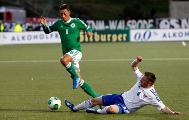 Germany's Mesut Ozil, left, is challenged by Faroe Islands' Suni Olsen during the group C World Cup qualifying soccer match between Faroe Islands and Germany in Torshavn, Germany, Tuesday, Sept. 10, 2013.  (AP Photo/Alvur Haraldsen)