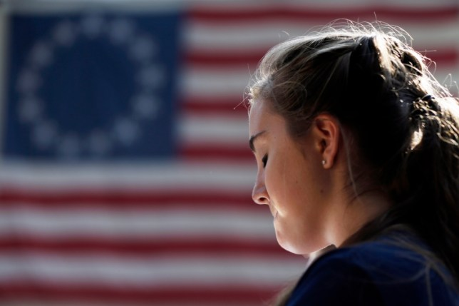 Isabella Webster, with the Council Rock High School South band of Holland, Pa., closes her eyes during prayer at a ceremony, Wednesday, Sept. 11, 2013, marking the 12th anniversary of the 9/11 terrorist attacks, at the Betsy Ross House in Philadelphia. (AP Photo/Matt Rourke)