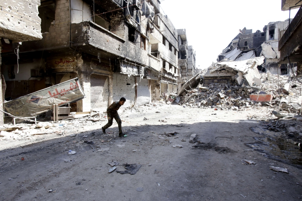 A fighter of the Popular Front for the Liberation of Palestine  General Command (PFLP-GC) runs across a street in the Yarmouk refugee camp in the Syrian capital Damascus on September 12, 2013, following fighting against rebels forces who control 75 percent of the camp. The PFLP-GC has been allied to Syrian President Bashar al-Assad's government whose troops have been fighting rebel forces for the past two years. AFP PHOTO/ANWAR AMROANWAR AMRO/AFP/Getty Images